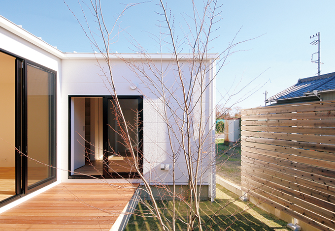 インフィルプラス【デザイン住宅、狭小住宅、平屋】パティオにはウッドデッキを設けてあり、四季を通じてオープンエアな開放感を満喫できる。右手のフェンスは、室外と室内の両方向からの視線を意識して高さを設定