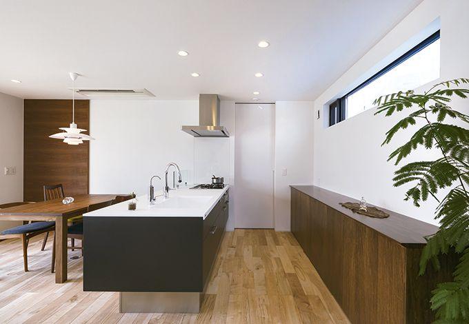 インフィルプラス【デザイン住宅、趣味、高級住宅】「LDKに生活感は出さない」という奥さまの信念のもと、キッチンには必要最低限の家具だけを配置。食器棚もフルオーダーで、LDKとの兼ね合いで調整したサイズ感が絶妙。冷蔵庫やレンジなど、家電はすべて奥のパントリー内に