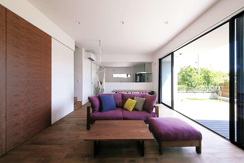 インフィルプラス【デザイン住宅、省エネ、間取り】クルミの無垢の床が素朴な温かみを感じさせるリビング。こげ茶色の引き戸の奥が和室。正面奥の対面キッチンは腰壁を高くして、作業の手元が見えないように配慮した