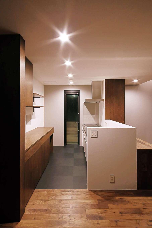 インフィルプラス【デザイン住宅、趣味、間取り】モルタル仕上げの腰壁で囲んだカウンター付きの対面キッチン。キッチンに立つと、ストリップ階段と庭が見渡せる