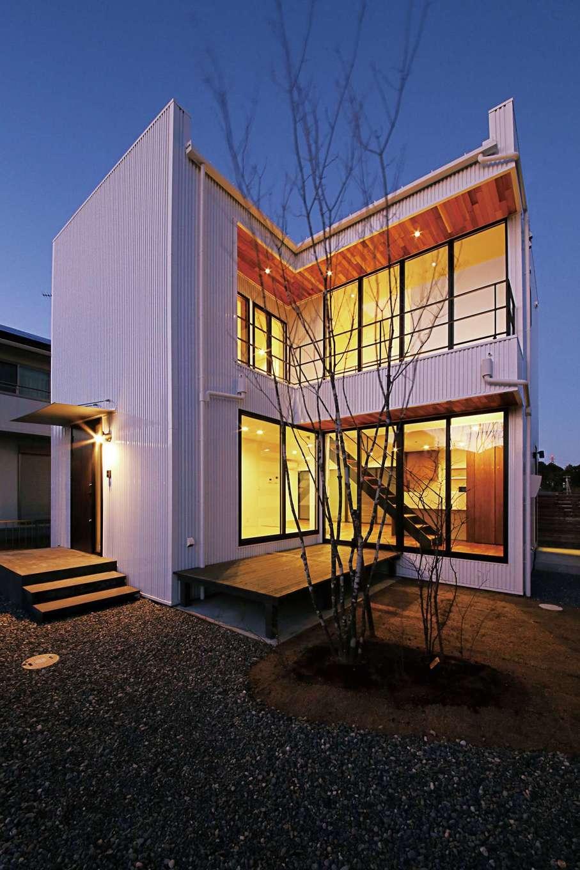 インフィルプラス【デザイン住宅、趣味、間取り】中庭に沿ってL字型に設けた大開口は、「SE構法」ならではの特権。夕闇に室内灯が映え、中庭やデッキを明るく照らす