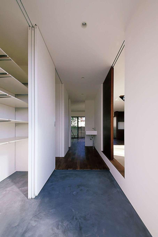 インフィルプラス【デザイン住宅、趣味、間取り】大きなシューズクロークのある玄関。右手には和室があり、土間から直接出入りできる。正面奥がリビング