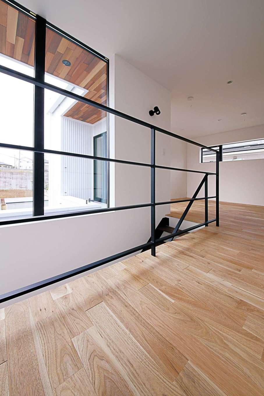 インフィルプラス【デザイン住宅、趣味、間取り】黒いアイアンの手すりのシンプルなラインが美しい階段ホール。2階の床はウォルナットのナチュラル色で統一