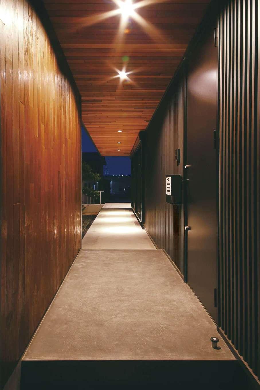 インフィルプラス【デザイン住宅、狭小住宅、間取り】旧宅にあった長い廊下の面影を残した、通し土間風のデッキ。床はコンクリート、壁の一部と軒天はレッドシダー張りにして、京の町家の軒先の風情を演出した