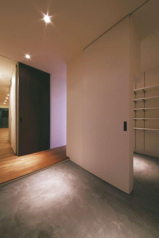 インフィルプラス【デザイン住宅、狭小住宅、間取り】モルタルの土間の玄関。大きな引き戸の奥にはシューズクロークと家族用の下足場がある