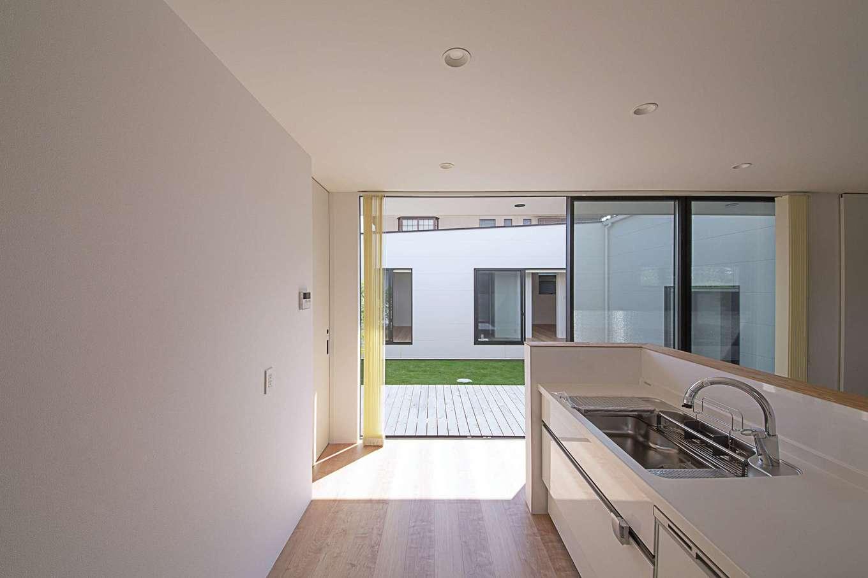 インフィルプラス【デザイン住宅、建築家、インテリア】リビングダイニングに向いた対面キッチン。ワークトップが隠れるように腰壁を高くしてある。サイドの掃出し窓から中庭と子ども部屋の様子を見渡せる