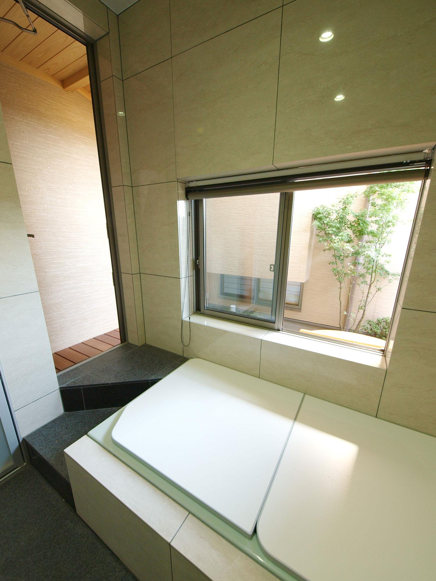 岩田建築【デザイン住宅、趣味、高級住宅】2坪近くある広いタイル張りの浴室。中庭に出られるドアがありここから露天風呂へ