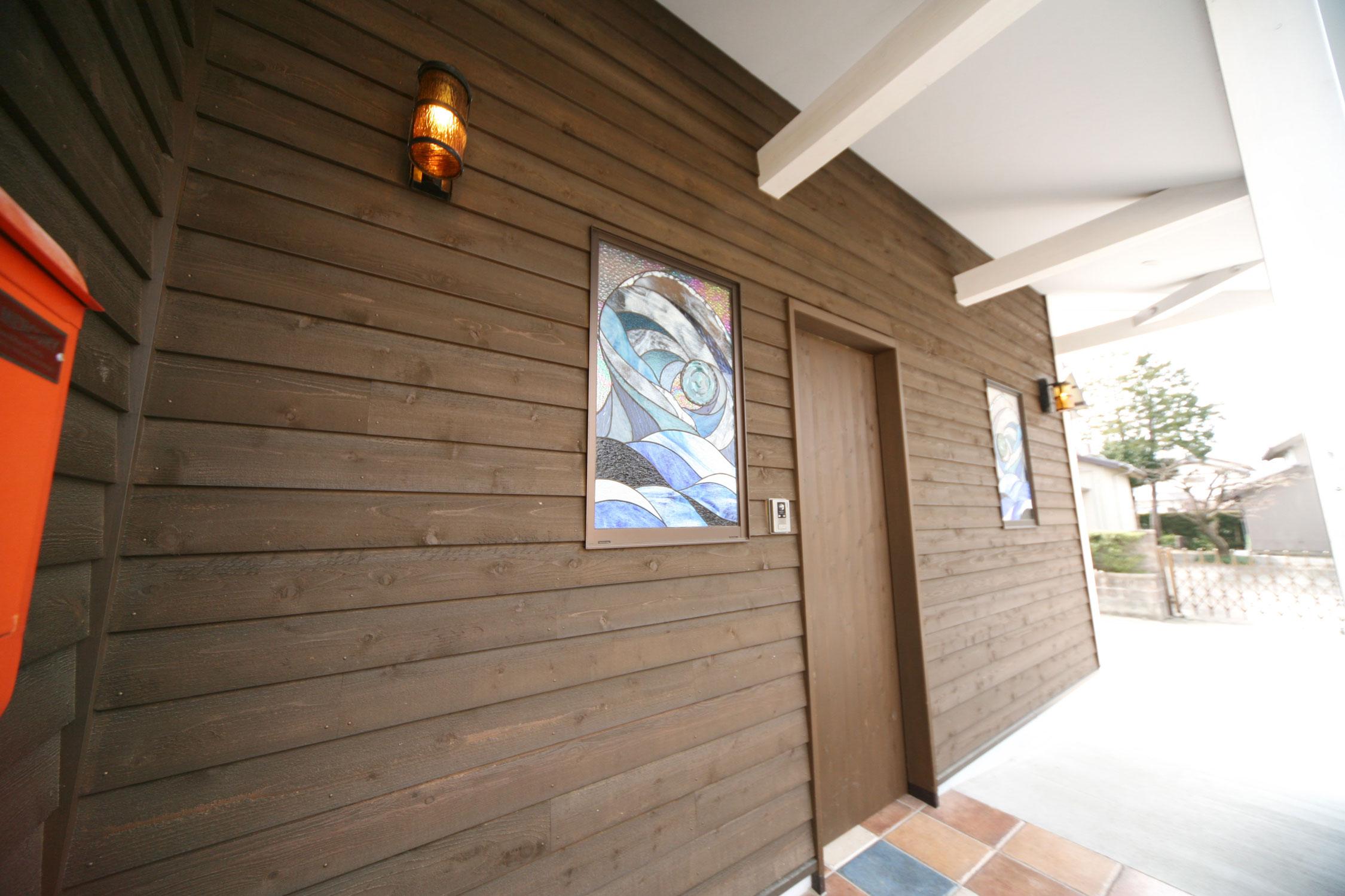 岩田建築【デザイン住宅、趣味、インテリア】ポーチ部分の外壁は板張り。木製玄関戸の両脇には、波をイメージしたオリジナルのステンドグラス