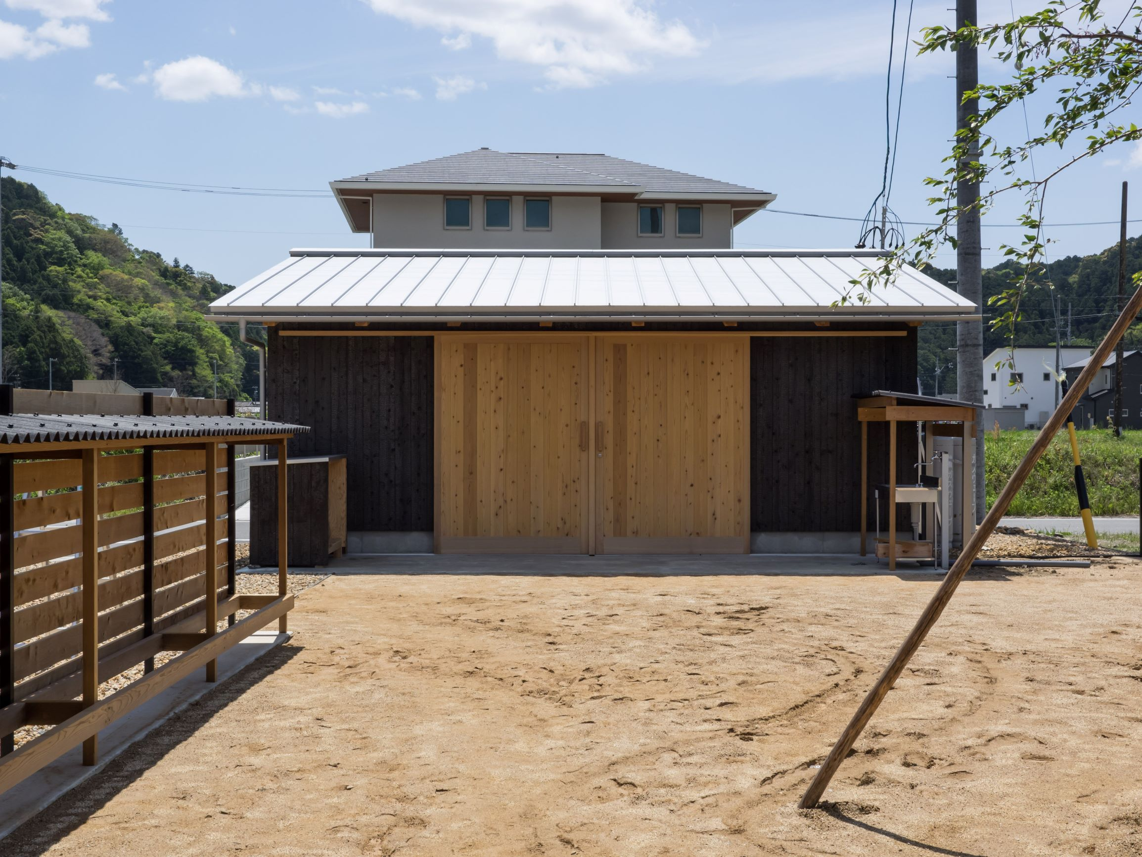 石牧建築【趣味、自然素材、平屋】中庭を挟んで、奥に見えるのが吹きガラス工房。大きな格子戸を介して、外と中のつながりを感じながらおおらかに暮らすことができる