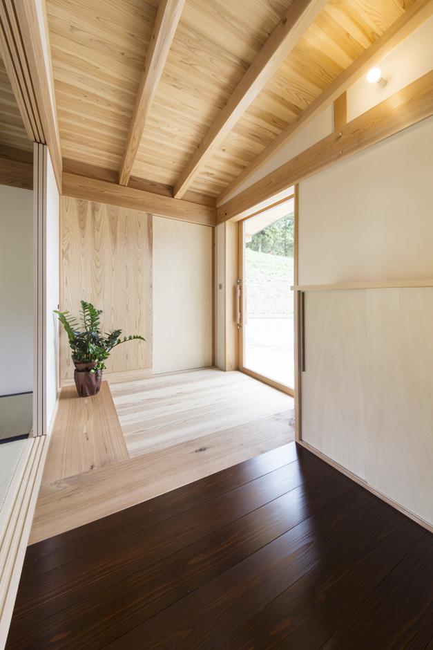 石牧建築【収納力、自然素材、建築家】玄関の土間部分は無垢の杉板。ここまでが土足で、木地になる栗の木のラインで靴を脱ぐ。段差はない。ガラスの玄関扉を採用したことで明るさも十分確保した