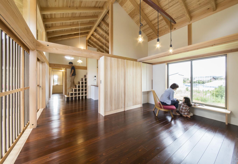 石牧建築【収納力、自然素材、建築家】垂木、Jパネルが現しとなり、天竜杉の香りが心地いいLDK。緑豊かな田んぼの景色を楽しむために、北面にも大きな開口部を設置した。艶やかに輝く無垢の床は、建築家と『石牧建築』のスタッフ、施主さん家族が一緒にワークショップで漆塗装を施した
