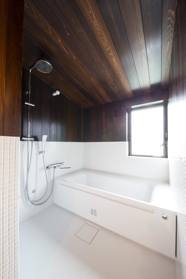 石牧建築【収納力、自然素材、建築家】勾配天井のハーフユニットバス。天井と壁は風呂桶に使われるサワラを漆塗りしたもの。雨に打たれる感覚のシャワーヘッドもマッチしている。和と洋が絶妙に融合した浴室は、極上のバスタイムを楽しめそう