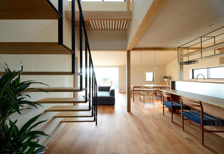北欧スタイルを意識した子世帯のLDK。ブラックチェリーの床に対して、カウンターや柱などにはクリやタモ、ナラといった異なる広葉樹を用い、それぞれの質感や表情の違いを楽しめる。アイアンやステンレスなどのメタリックな素材をアクセントに用い、甘さを抑えたスタイリッシュな空間を演出