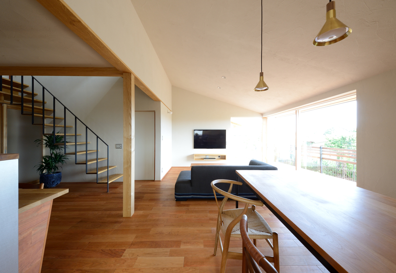 壁と勾配天井は同社オリジナルの珪藻土仕上げ。テーブル、ソファ、TVボードも同社の造作家具。リビングの南側にはL字型の開口部とデッキを設けてあり、デッキに出ると親世帯の玄関や庭景色が見渡せる
