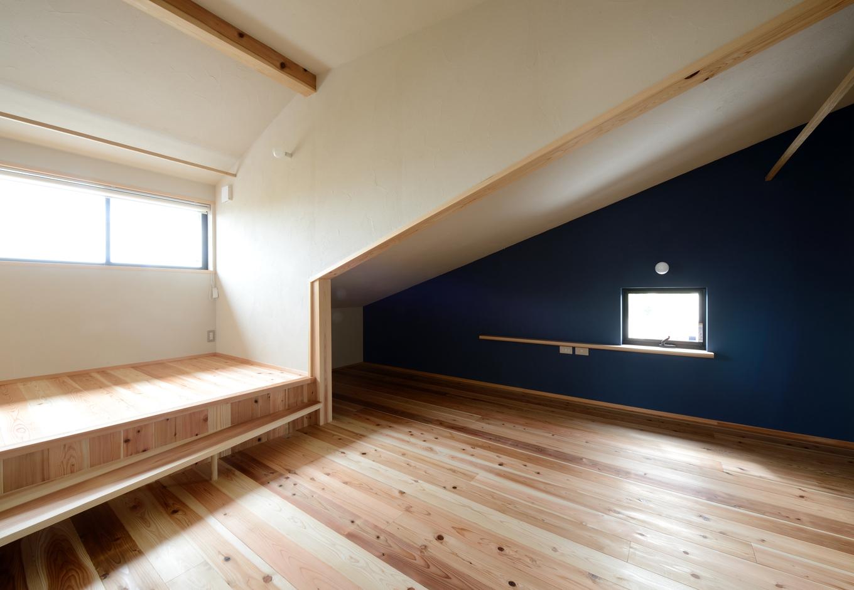 2階の寝室。天井の低い部分は気持ちが落ち着きやすいので、寝る場所に利用。西側の壁一面を紺色に塗り、穴蔵のような「こもり感」を演出した。天井が高い方には小上がりのスペースを設けてあり、床や天井の高低差がリズミカルな楽しさを感じさせる