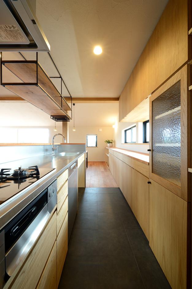 オリジナルのキッチンと収納棚。年に数回、親戚が25人程集まる機会があるため、ミーレ社製の大型の食洗機を採用した。オリジナルの吊り棚にはワインバーのようにワイングラスを吊るしておけるようになっている