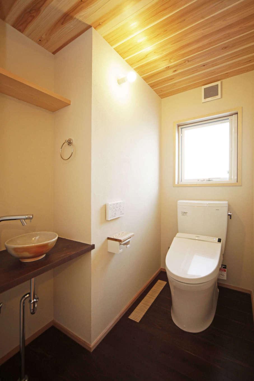 石牧建築【デザイン住宅、子育て、自然素材】トイレの床は、杉の板に漆を塗って防水性を高めている。手洗い鉢は、地元遠州の陶芸作家のもの
