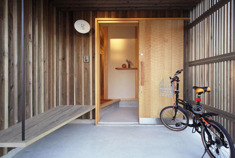石牧建築【デザイン住宅、子育て、自然素材】北側に位置する玄関ポーチだが、格子から光が差し込むことで十分明るい。独特のけずり跡が残る日本古来の伝統技術「なぐり加工」を施した玄関扉、アイアンの手すりがついたベンチなど、こだわりが光る