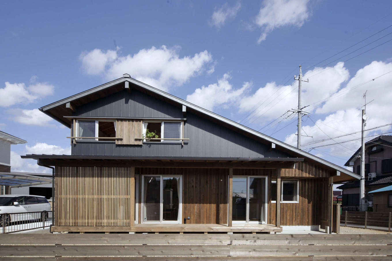 石牧建築【デザイン住宅、子育て、自然素材】道路側から見たときの美しさにこだわったファサードと大屋根が目を引く。杉板とガルバリウム鋼板の異素材を組み合わせたデザインもユニーク。夜にはスリットから温かな光がこぼれる