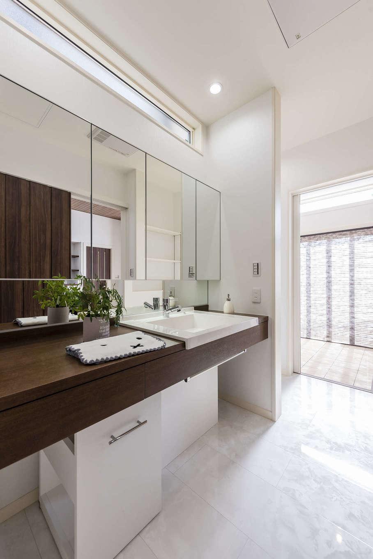 白い大理石調のフロアパネルを用いて、清潔感溢れる洗面脱衣所。全面鏡張りで広がりを感じる。物干しもできるサンルームに直結しているので、洗濯の負担が軽減できる家事ラク動線