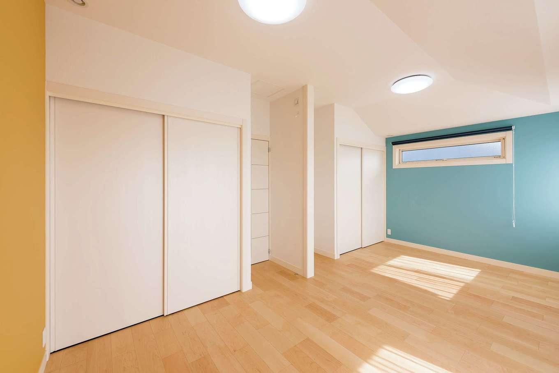 勾配天井とアクセントクロスで遊び心を取り入れた子ども部屋。壁で仕切り、2部屋として使うことも可能。将来の家族構成の変化にも対応できる