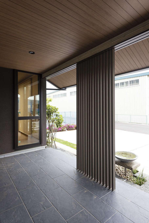 ミサワホーム静岡【デザイン住宅、和風、省エネ】玄関ポーチからリビング前まで大きく張り出した軒には、木質パネルを使用。玄関周りには石材やデザイン性のある格子を配し、家の顔にふさわしい品格を備えた