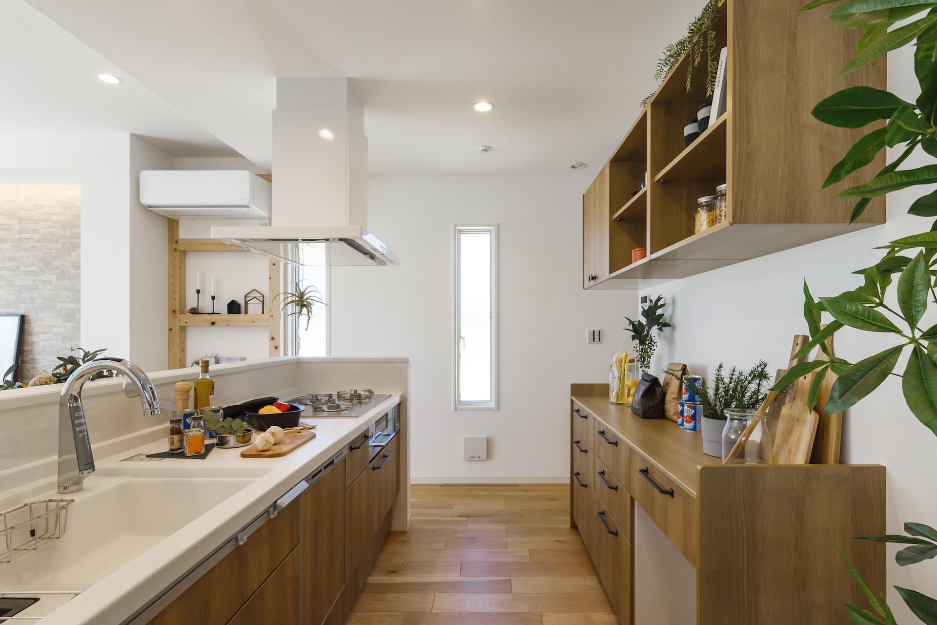 ミサワホーム静岡【デザイン住宅、収納力、インテリア】みんなで料理をするなら、オープンな対面式のキッチンがおすすめ。キッチンを囲んで視線を合わせながら作業ができるので、ふれあいながら楽しく準備ができる。こだわりのマグカップやポットをディスプレイできるよう、あえてオープン収納にしたカップボードは、おしゃれに見せたいところ