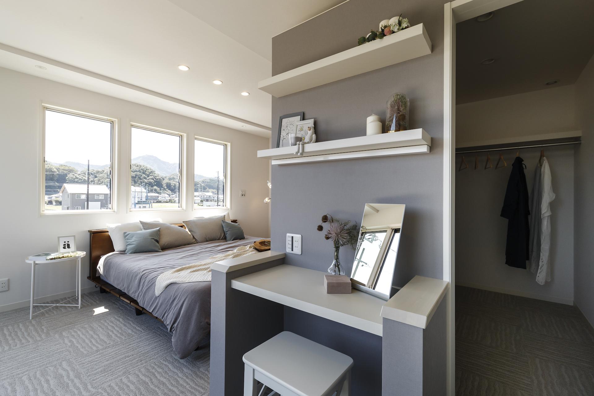 ミサワホーム静岡【デザイン住宅、収納力、インテリア】グレーのアクセントクロスが印象的な寝室。1階とは少し趣味を変えて、優しい印象のお部屋に仕上げた。床面には足音を抑えられるカーペットを採用。保温効果も期待できるので、眠る前に足元が冷えずに快適