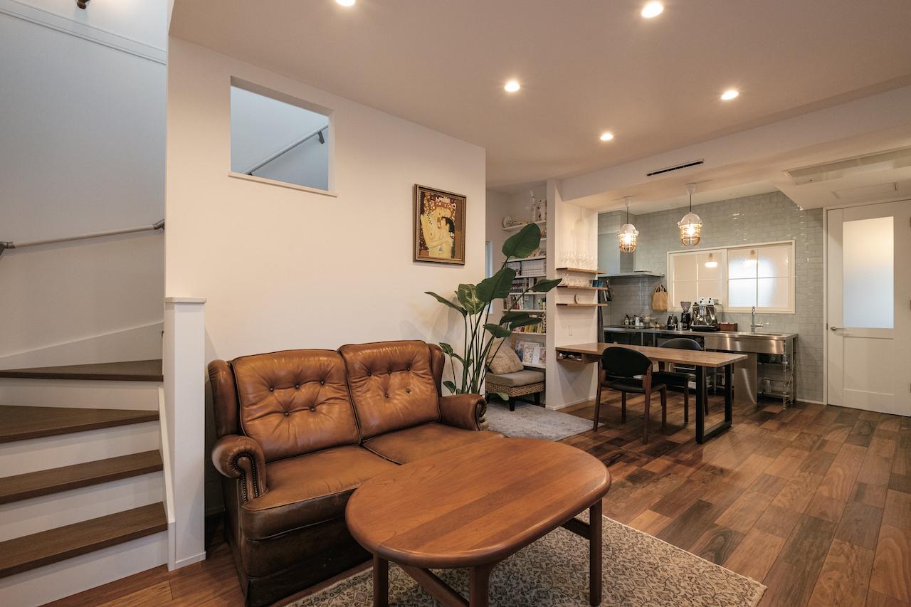 OWN RESORT HOME(オウンリゾートホーム)【1000万円台、デザイン住宅、インテリア】ソファとテーブルは定額に含まれ、Sさんが直感で選んだそう。壁に開けた内窓が階段の吹き抜けから1階に光を運ぶ。ダイニングテーブルは壁に付けて造作し、床の色に合わせて塗装。その横に本棚を造作した