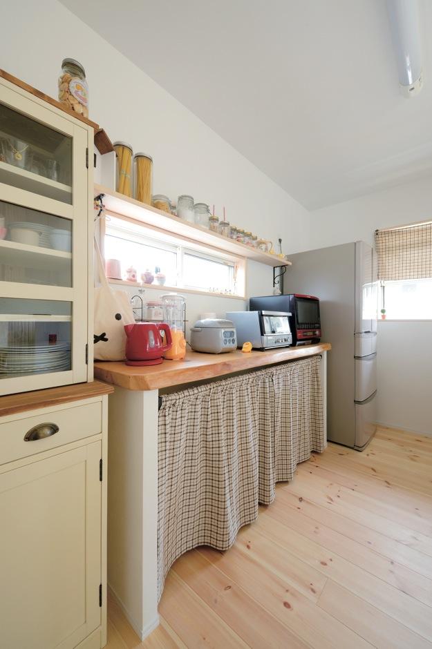 アキケンチク【1000万円台、子育て、自然素材】無垢の一枚板が圧倒的な存在感を放つキッチンのバックヤードは、冷蔵庫や食器棚のサイズに合わせて造作。カーテンでゴミ箱を隠す工夫も