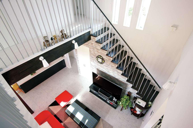 階段部分に設けた縦のスリット窓と、反対側のバルコニー側の窓が、1階のリビングに光を届ける。吹き抜けを見下ろす廊下はリゾート地にある邸宅のような高級感と家族のつながりをもたらしてくれる
