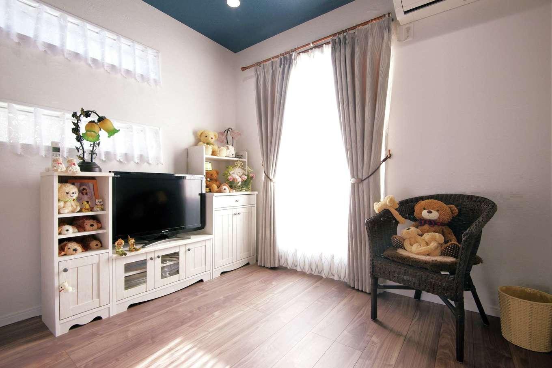 寝室は木目調の床とネイビーのクロスを貼った天井で落ち着いた雰囲気に。バルコニーには廊下だけでなくこちらからも出入りできる