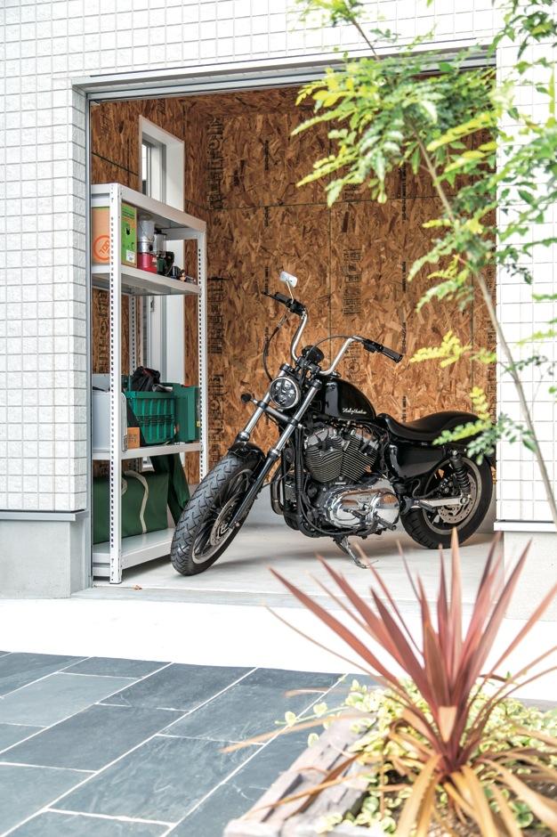 アフターホーム【1000万円台、デザイン住宅、趣味】大型バイクが収まるガレージ。子ども部屋にエンジン音が響くのを防ぐため、2階部分にはご主人の書斎を配置。中庭と往き来もできる開口部も設けた