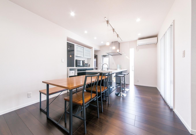 アフターホーム【1000万円台、子育て、ガレージ】シンプルなカウンターキッチンには、ハイスツールをあつらえて。白と黒のモノトーンはご主人のチョイス。背面には収納家具がちょうど収まる寸法でスペースを作ってある。キッチンと色を統一しているので、すっきりとした印象