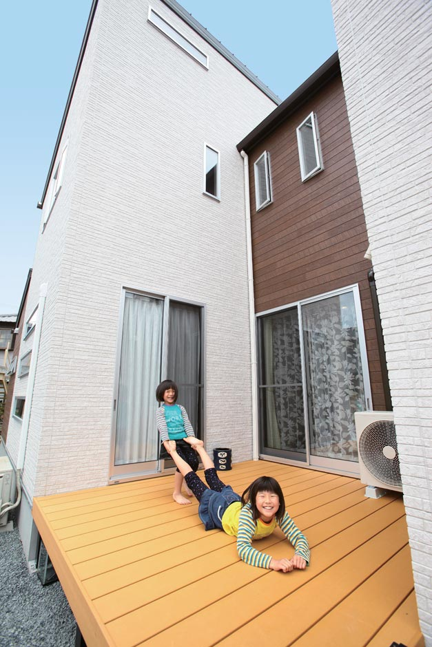 内庭兼アウトドアリビングとしても利用できる案をしてもらえる ウッドデッキ。ここから見上げる家の形がご主人 のお気に入りのスポット。今は空き地になって いる横の土地に家が建っても、ウッドデッキが暗 くならないように、2階バルコニーの一部の柵を 磨りガラスにしているそう