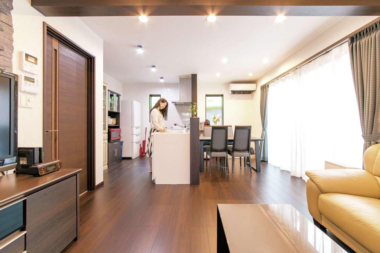 奥さまがキッチンに立つ際に、ご主人や子どもたちが冷蔵庫の飲み物を取りに来ても、楽にすれ違える幅を確保したキッチン。空間の色調に合わせてチョイスしたカリモクのテーブルセットが、大人のダイニングを演出