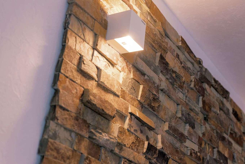 アフターホーム【1000万円台、デザイン住宅、間取り】リビングのテレビボードの背面の壁に用いたのは、石材タイル。これにより真っ白な空間にインパクトとリゾートホテルのような高級感をプラスしている。ランダムな色と形は自然のままに。間接照明の陰影もインテリアのひとつになる