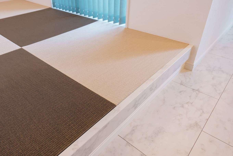 アフターホーム【1000万円台、デザイン住宅、間取り】畳コーナーの立ち上がりにまで真っ白な大理石調のパネルを敷き詰めたLDK。木材とはまた違った、個性的な空間を演出できる。白いベースはアクセントに用いるカラーを限定しないので、家具やファブリック、畳の色まで自由に選べる