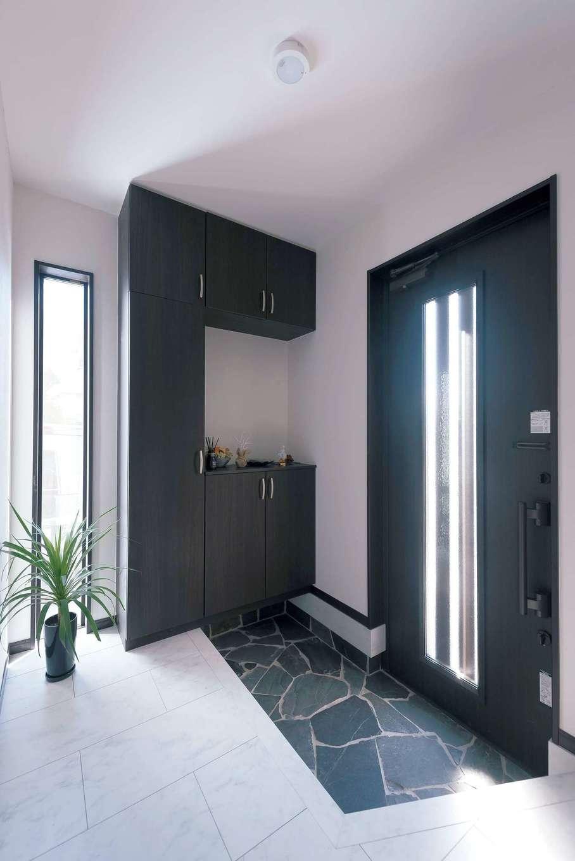 玄関は自然石の乱貼りで高級感のある仕上がりに。採光とデザインを兼ねた縦スリット窓もおしゃれ