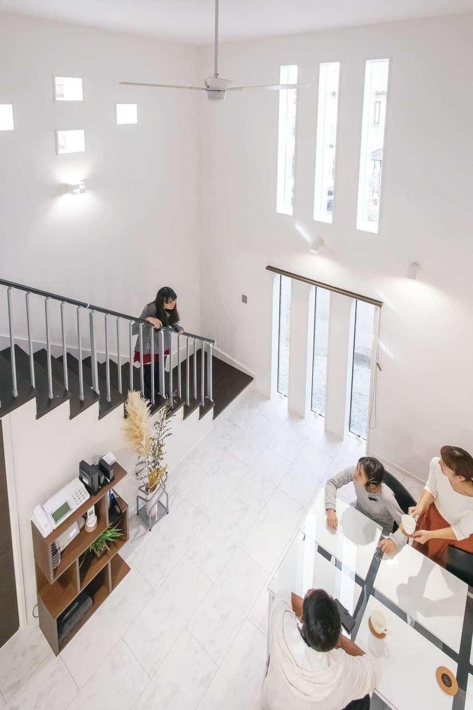 アフターホーム【デザイン住宅、二世帯住宅、間取り】リゾートホテルのような心地よさをもたらす吹抜けのダイニング。三連のスリット窓でプライバシーを守りながら開放的に過ごせる。デザイン階段がアクセントに