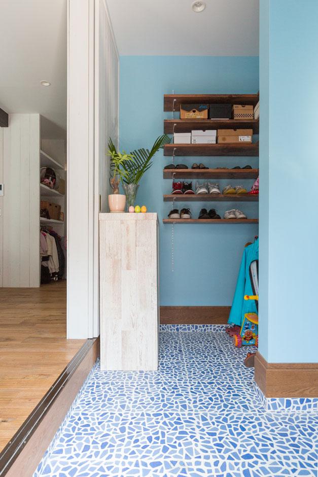 透き通った海を思わすような玄関のタイルが印象的。フルオープンになる引き戸を開けて、そのままリビングへ。シューズクローゼットは、棚とハンガーポールですっきりとした収納空間。LDKと揃えたライトブルーの壁で明るい空間に