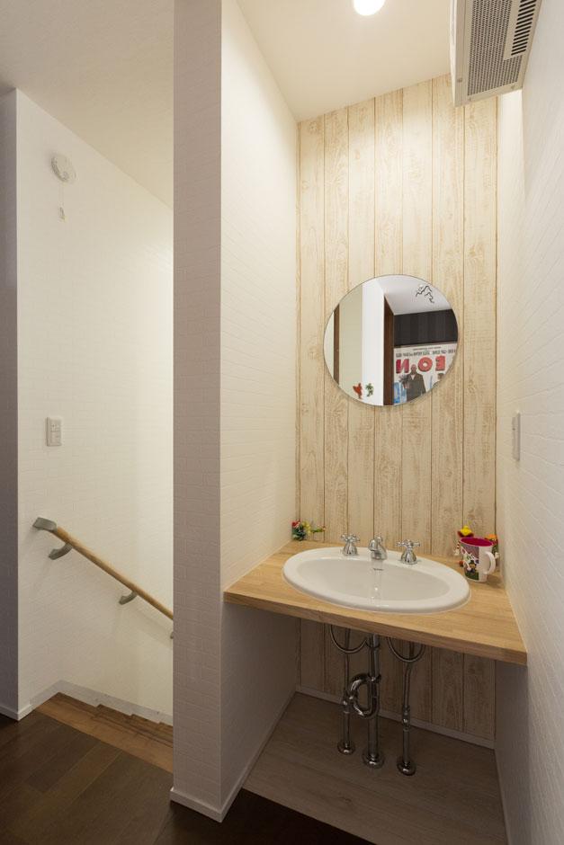 丸い洗面ボウルと鏡、レトロな水栓がかわいい洗面スペース。シンプルな天板のみの洗面台が清潔感をもたらす。ダークカラーのフロアとのコントラストも絶妙