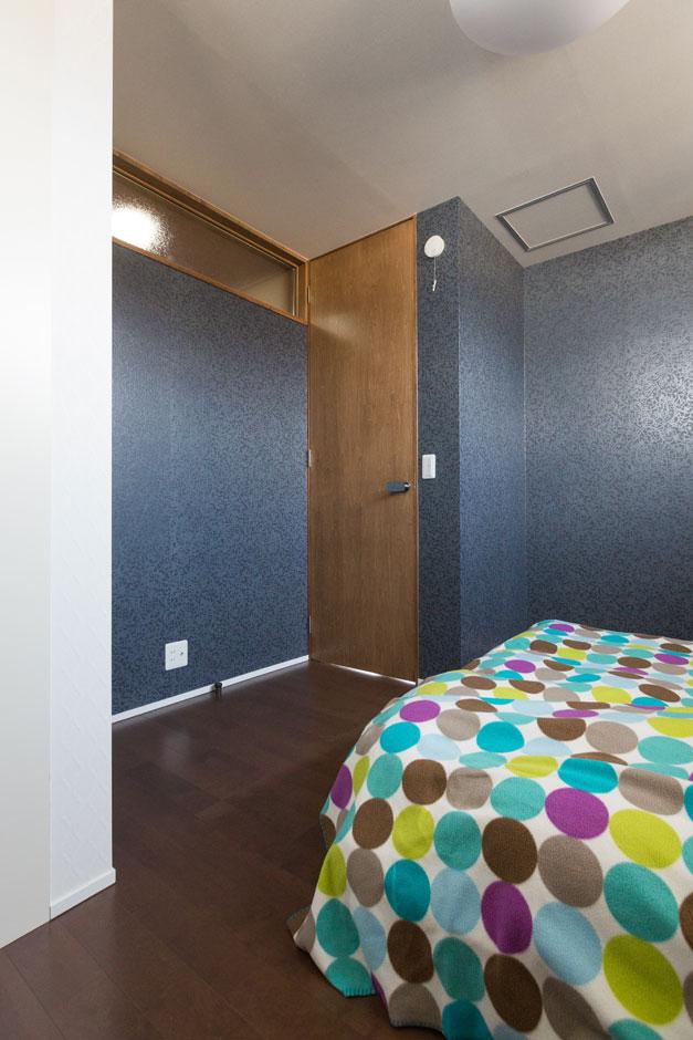 寝室はエンボス加工のシックな色調のクロスをアクセントに。天井まで届くハイタイプのドアで、縦空間の広がりを感じさせる。壁の上部に儲けたガラスのフィックス窓は、隣の空間への明かり取りの役割も