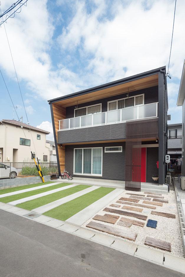 西川建設~Life is Dream~【デザイン住宅、趣味、自然素材】上部に向かって張りだすようなフォルムと、米杉のニュアンスある色調、赤い玄関ドアが目を引く外観。目隠しを兼ねた玄関の格子が個性的な表情をプラスしている。アプローチには枕木を敷いて来客を迎える