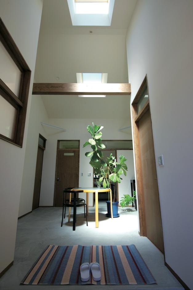 西川建設~Life is Dream~【デザイン住宅、自然素材、間取り】玄関を入ると目の前に広がる吹き抜けのフリースペース。建物の中心にあるため、天窓から入る光が ドア上の窓から各部屋に明るさをもたらしてくれる