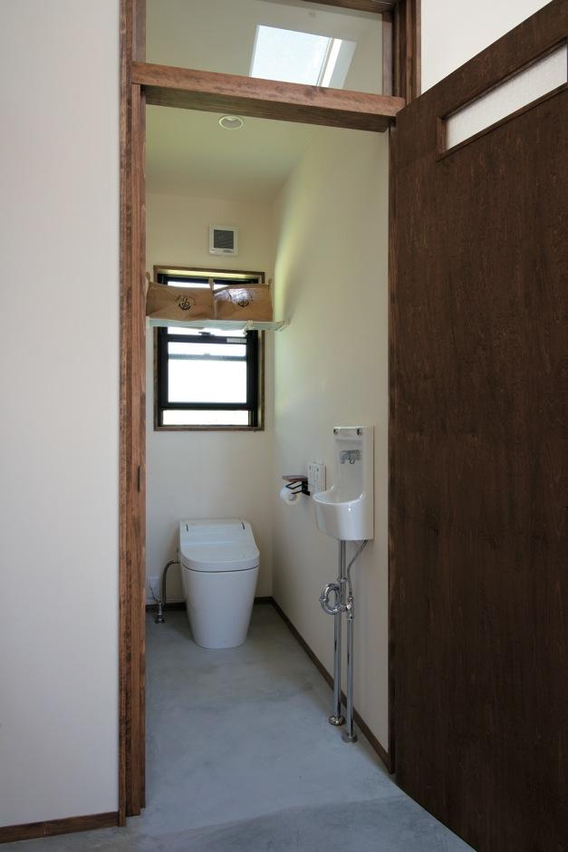 トイレの床もフリースペースと同じモルタルに。ドアもこの家の雰囲気に合わせて製作した