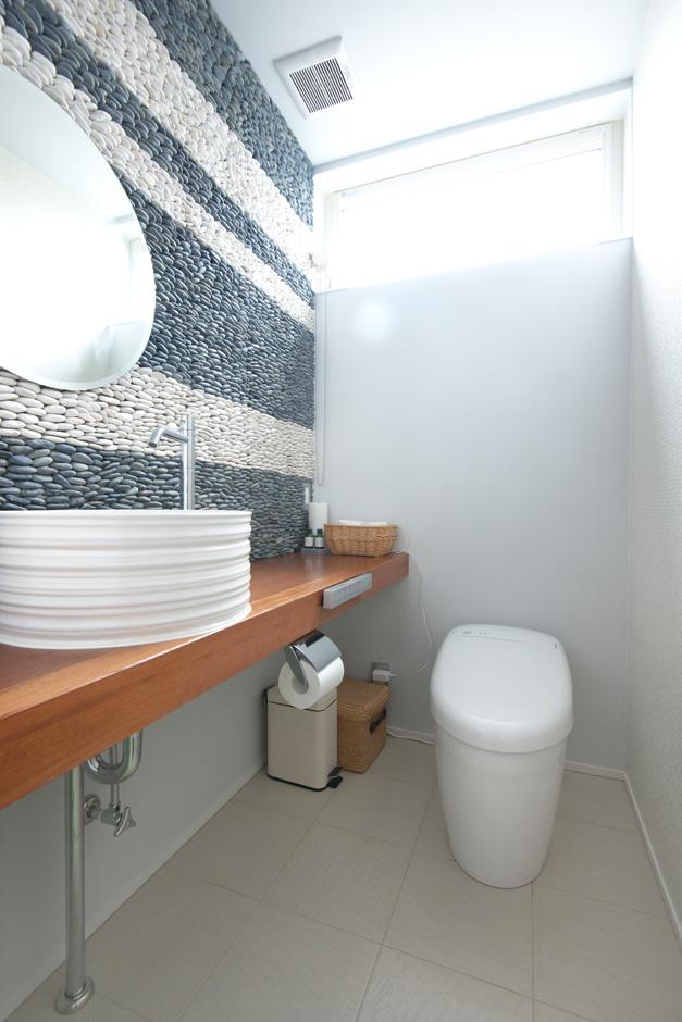西川建設~Life is Dream~【デザイン住宅、自然素材、高級住宅】本物の石でできた壁のパネルが印象的なトイレは、床がタイルで掃除がしやすい為奥さまの家事ラクを実現