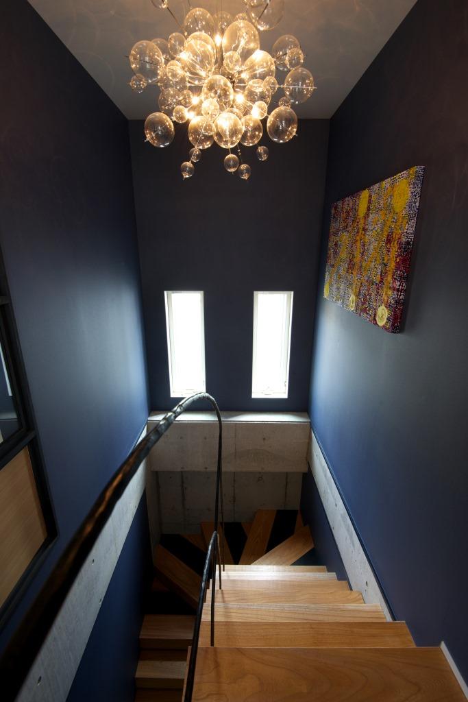 西川建設~Life is Dream~【デザイン住宅、自然素材、高級住宅】無垢のケヤキを使った階段はアイアンの手すりをアクセントに。壁に飾られたパネルがお家の個性を引き立てている