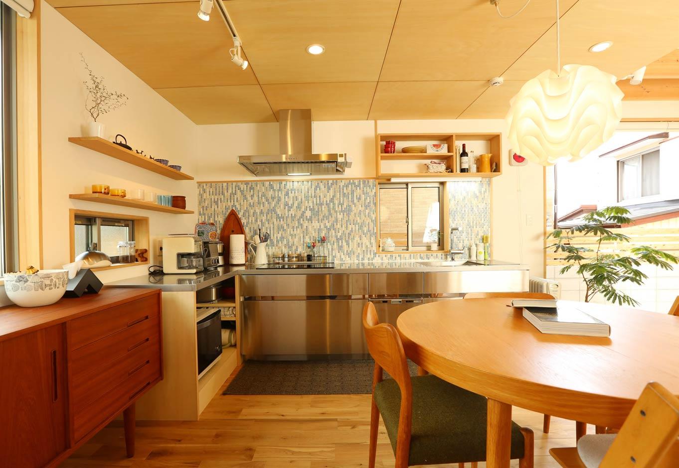 Asobi-創家(アソビスミカ)/ナカジツ【狭小住宅、間取り、建築家】オールステンレスのおしゃれなキッチンは奥さまからのリクエスト。L字型にすることで空間を広く使えると同時に作業効率もUP! 2面採光で明るさを確保し、名古屋モザイクの上質なタイルが料理タイムを楽しく演出する。キッチンの高さに合わせて収納棚を造作した