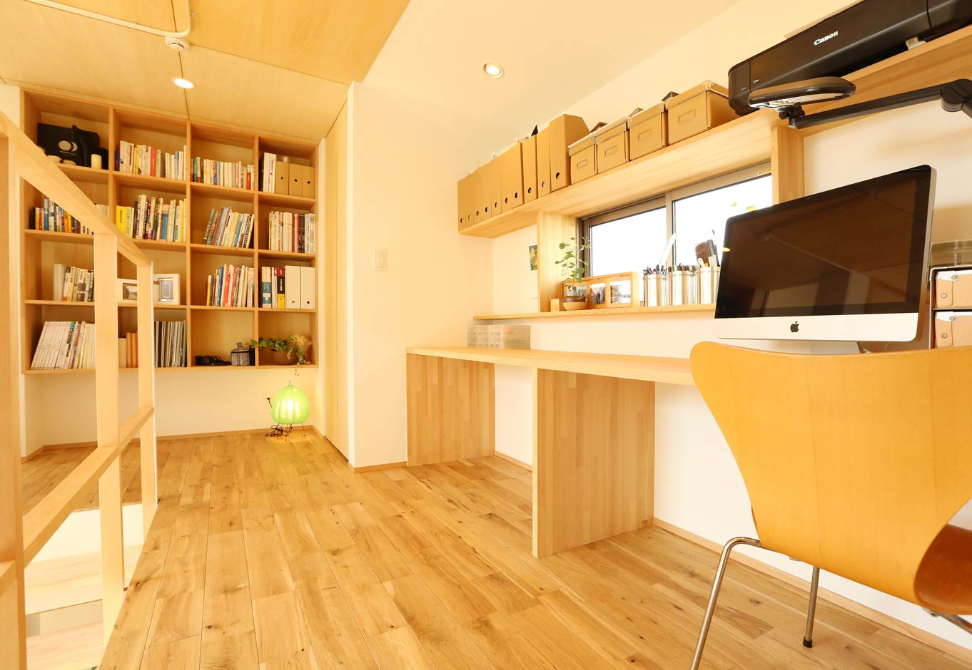 Asobi-創家(アソビスミカ)/ナカジツ【狭小住宅、間取り、建築家】2階のファミリースペースは、吹抜けを通して1階と会話できるので、お互いのコミュニケーションが取りやすい。壁一面の大きな本棚とカウンターを造作し、子どもたちはここでお勉強。1階同様、2階の天井にもシナベニヤを貼り、木のやさしい雰囲気を醸し出している